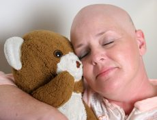 a medical patient cuddling with a teddy bear for comfort.