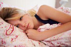 Worried Teenage Girl Lying In Bed
