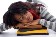 tired school girl sleeping with her books against white background